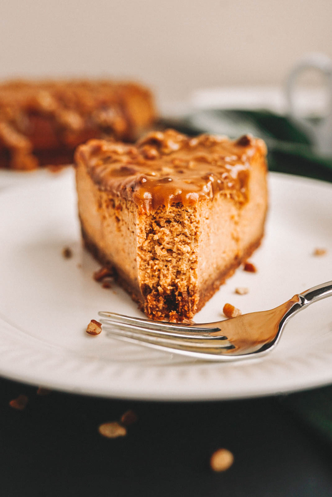 A slice of pumpkin cheesecake topped with maple pecan sauce on white plate on a black background