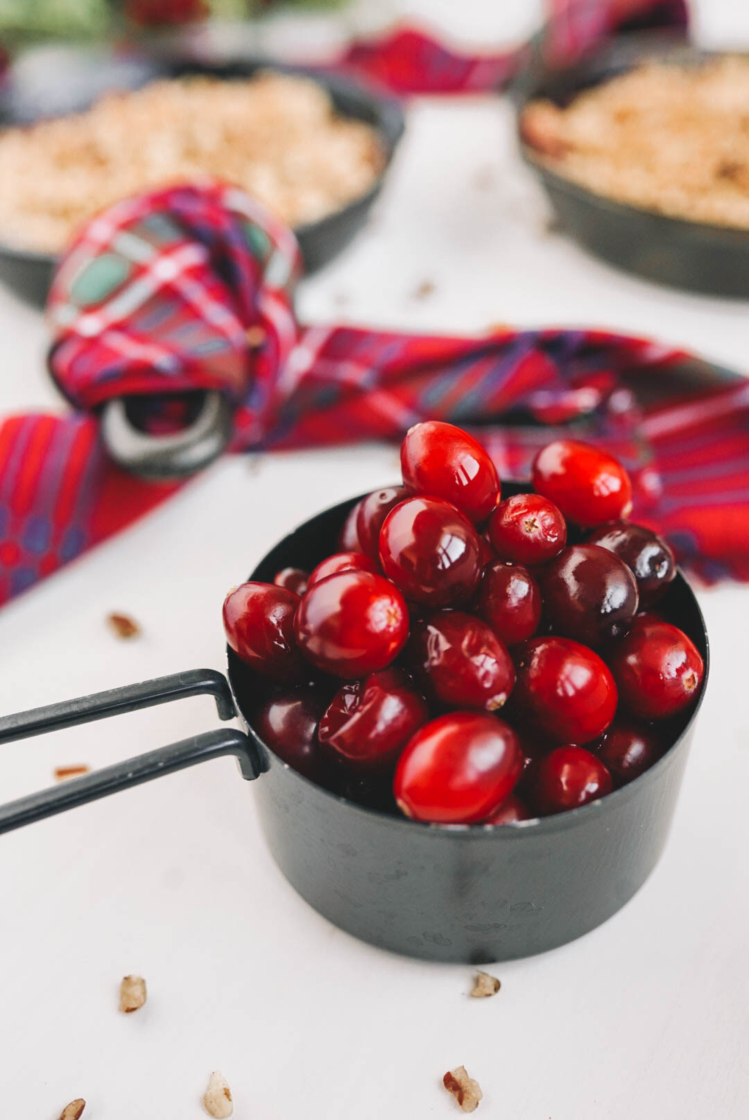 cranberries in black measuring cup skillet with plaid dish towel on white surface