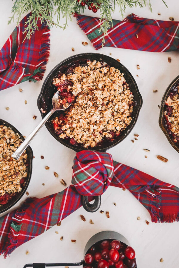 apple cranberry crisp in cast iron skillet with plaid dish towel on white surface