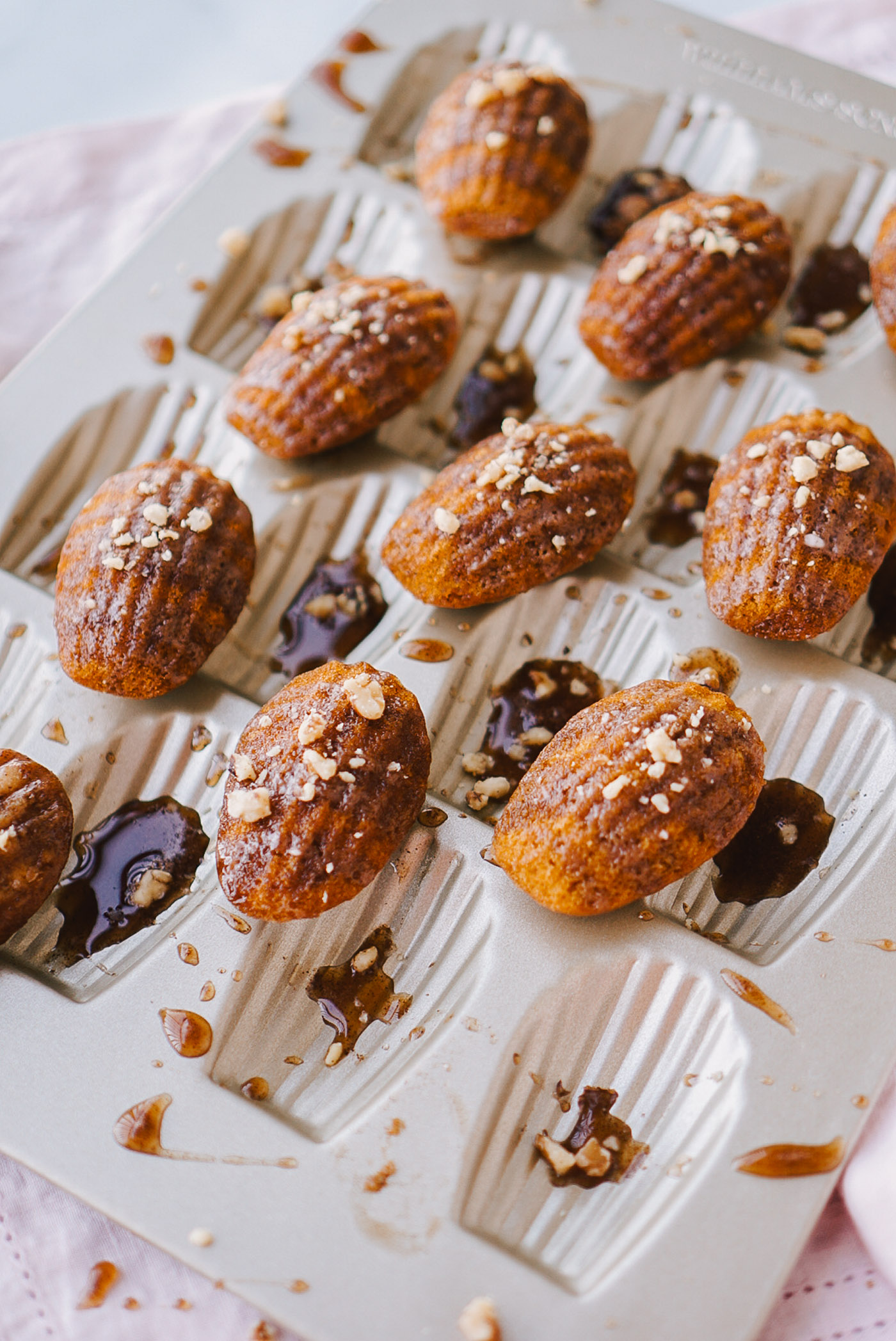 pumpkin spice madeleines on gold madeleine pan topped with maple glaze and chopped pecans sitting on pink fabric napkin