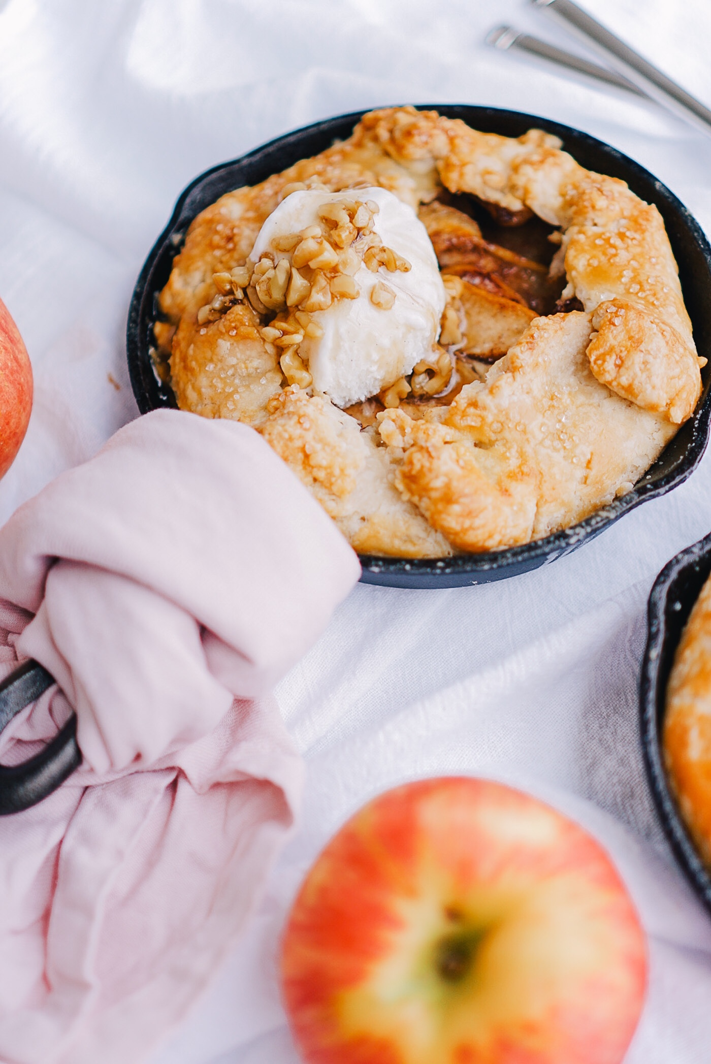 Easy apple pies in small cast iron skillets with light pink dish towel on white backdrop.