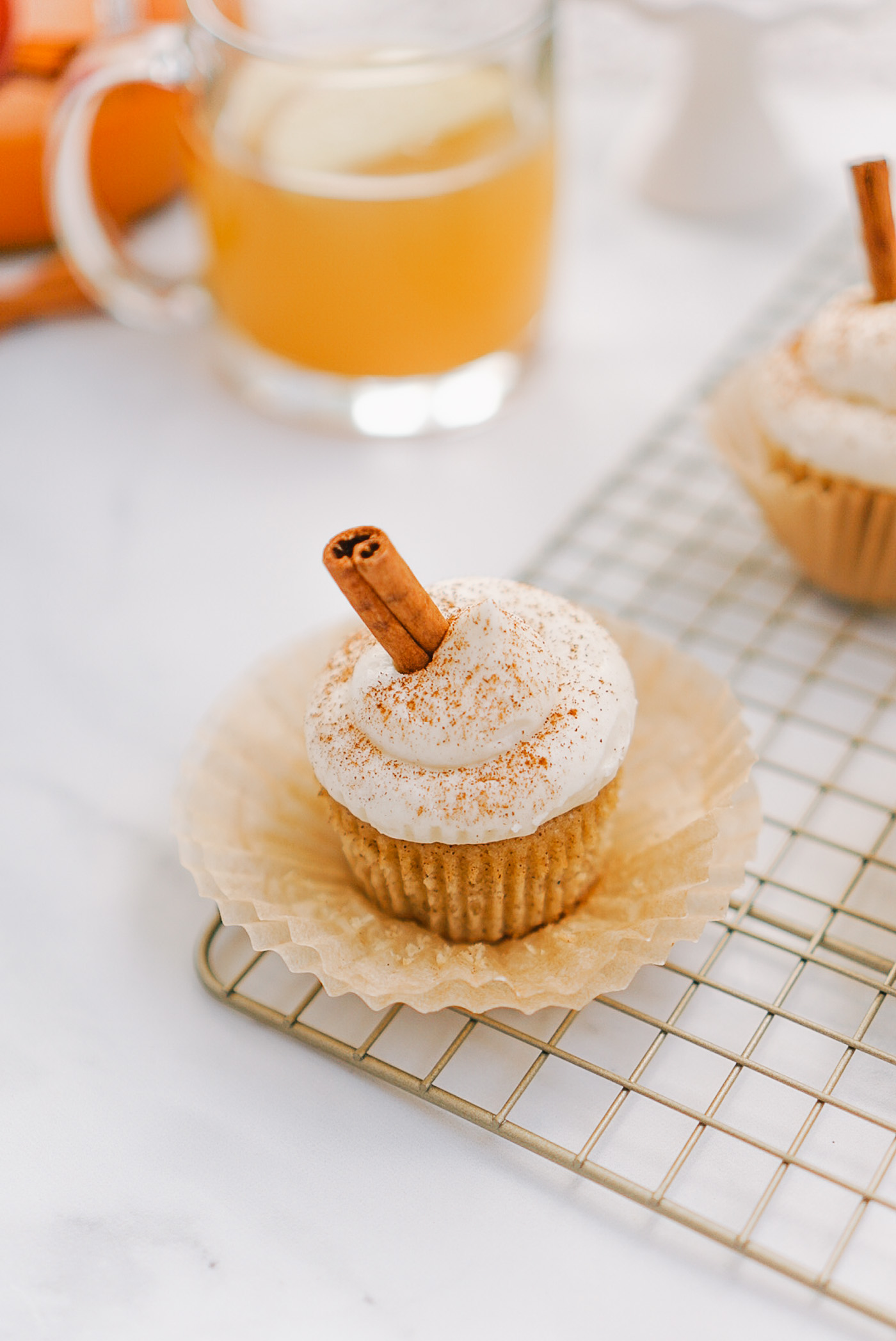 Apple cider cupcakes with cream cheese frosting and a cinnamon stick on gold cooling rack on white surface.