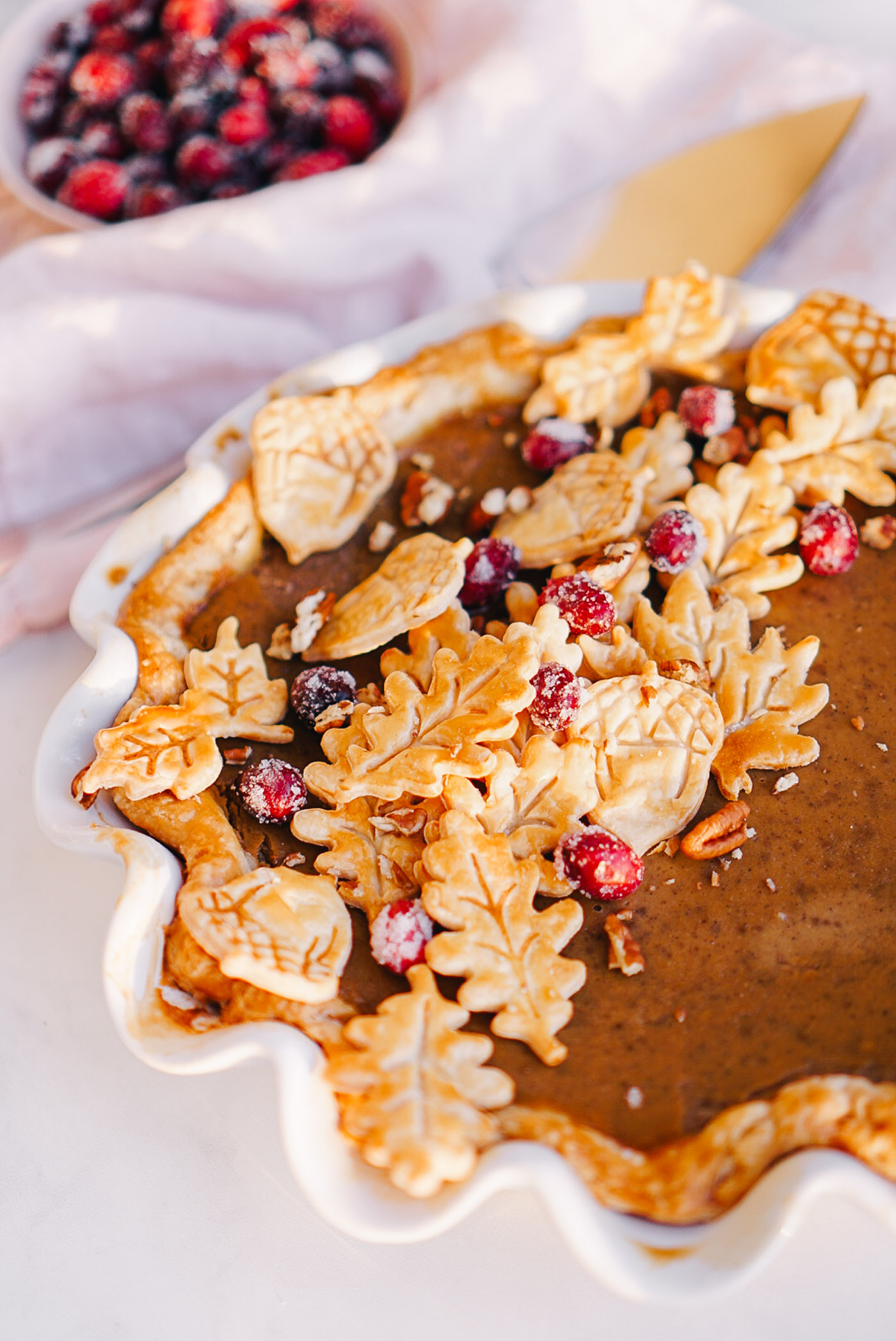 maple pumpkin pie topped with pie crust leaves and sugared cranberries in white ruffle dish