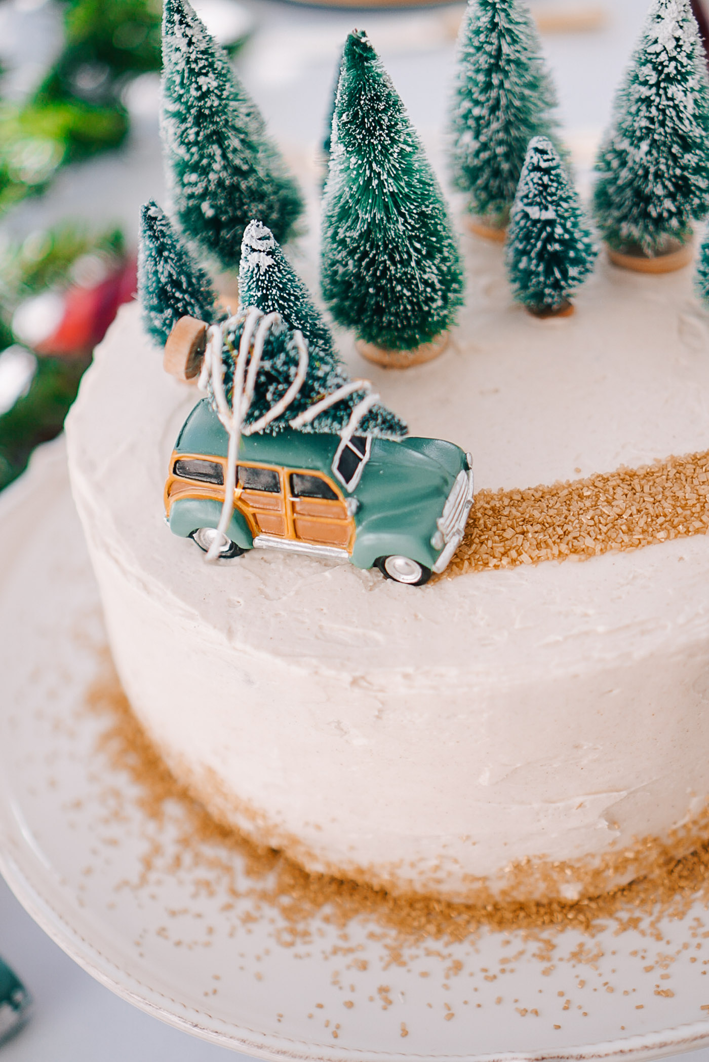 Gingerbread cake with buttercream frosting, Christmas trees, and a station wagon on white cake plate