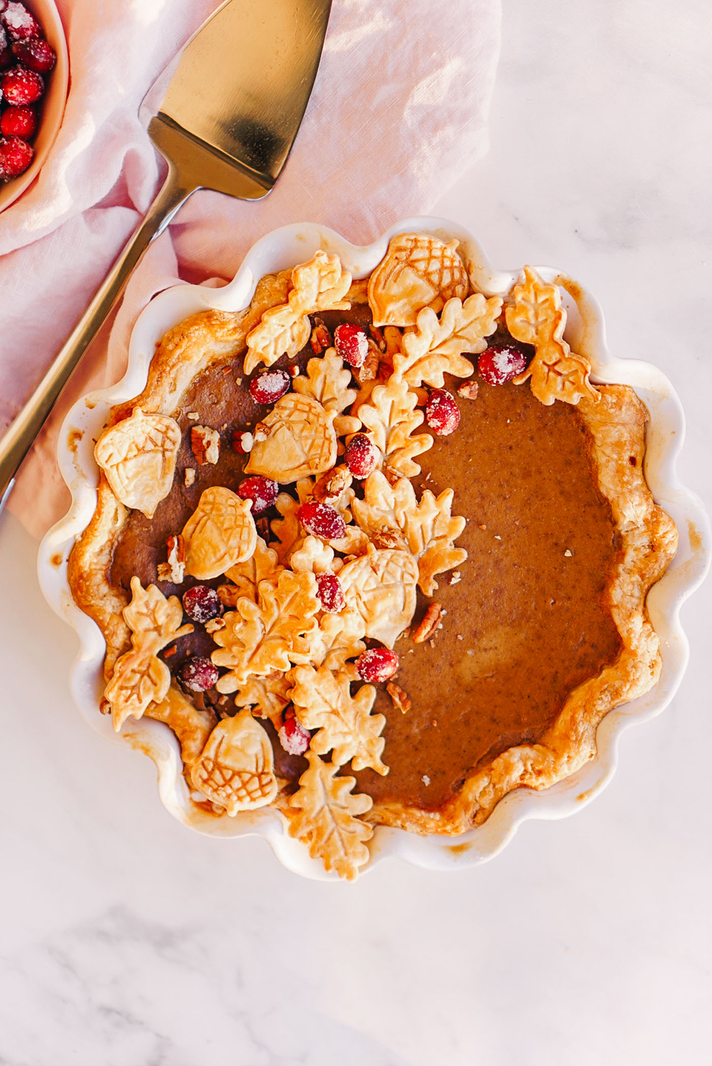 maple pumpkin pie topped with pie crust leaves and sugared cranberries in white ruffle dish on light pink dish towel
