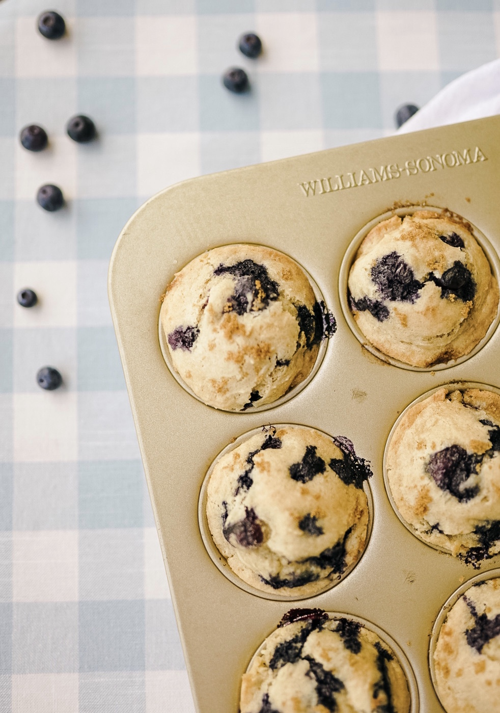 gluten free blueberry muffins in gold muffin tin with fresh blueberries on a blue gingham tablecloth