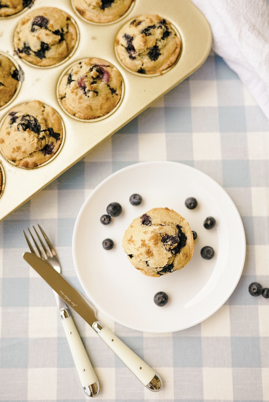 gluten free blueberry muffin on small white plate with fresh blueberries on a blue gingham tablecloth