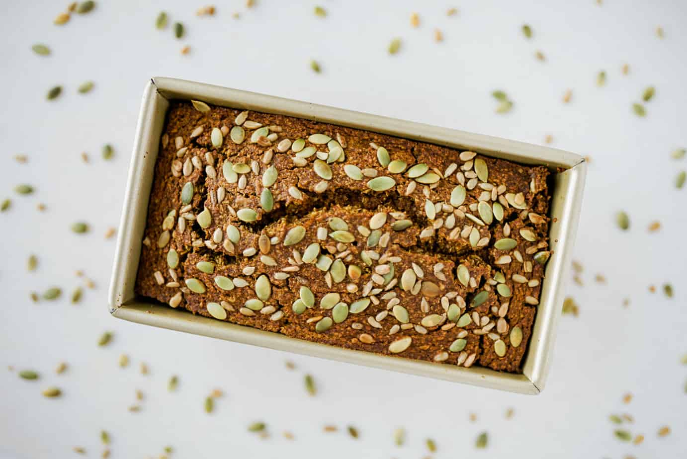 healthy pumpkin bread with pumpkin seeds sprinkled over top sliced on white countertop