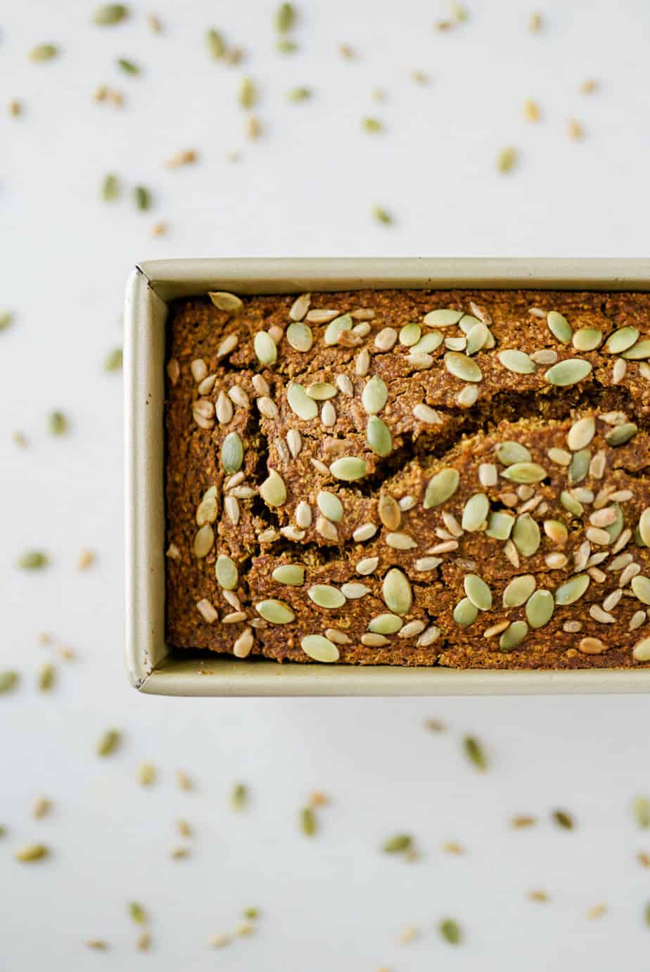 healthy pumpkin bread in gold loaf pan with pumpkin seeds sprinkled over top on white countertop