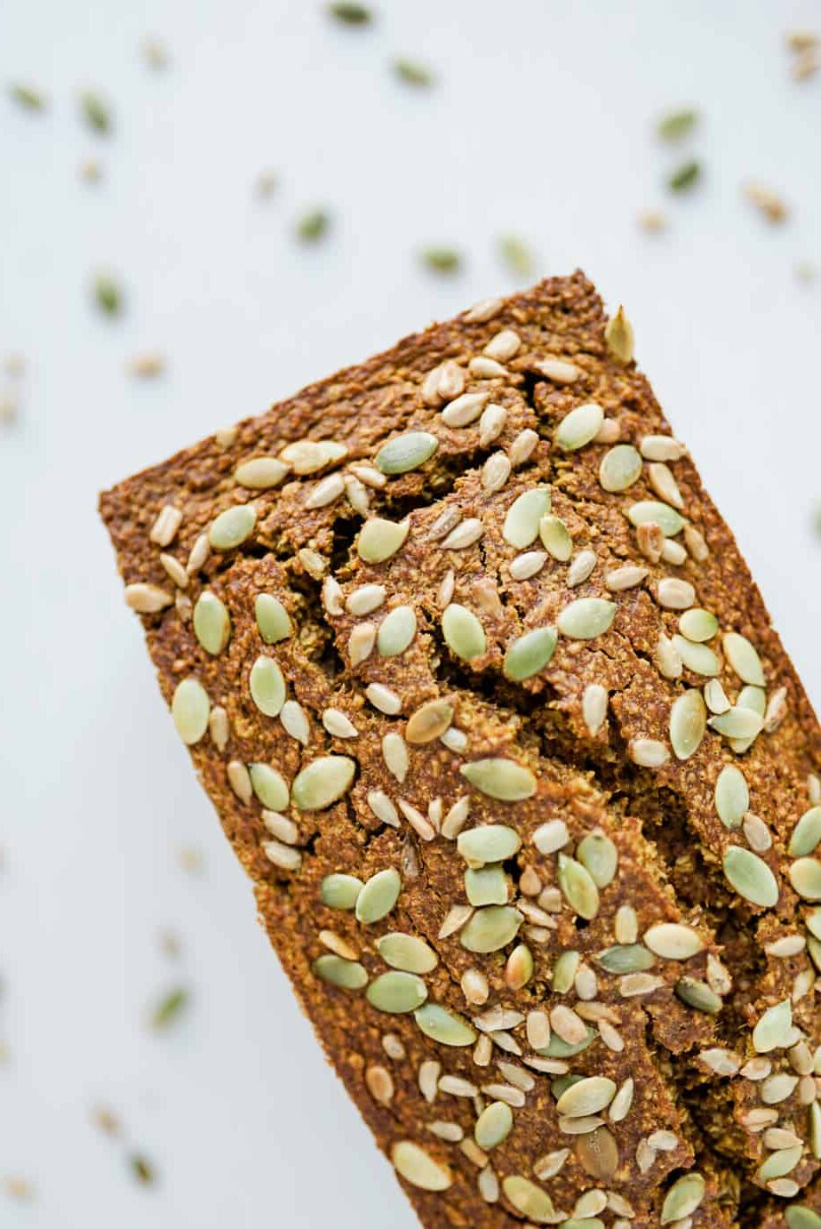 healthy pumpkin bread with pumpkin seeds sprinkled over top on white countertop