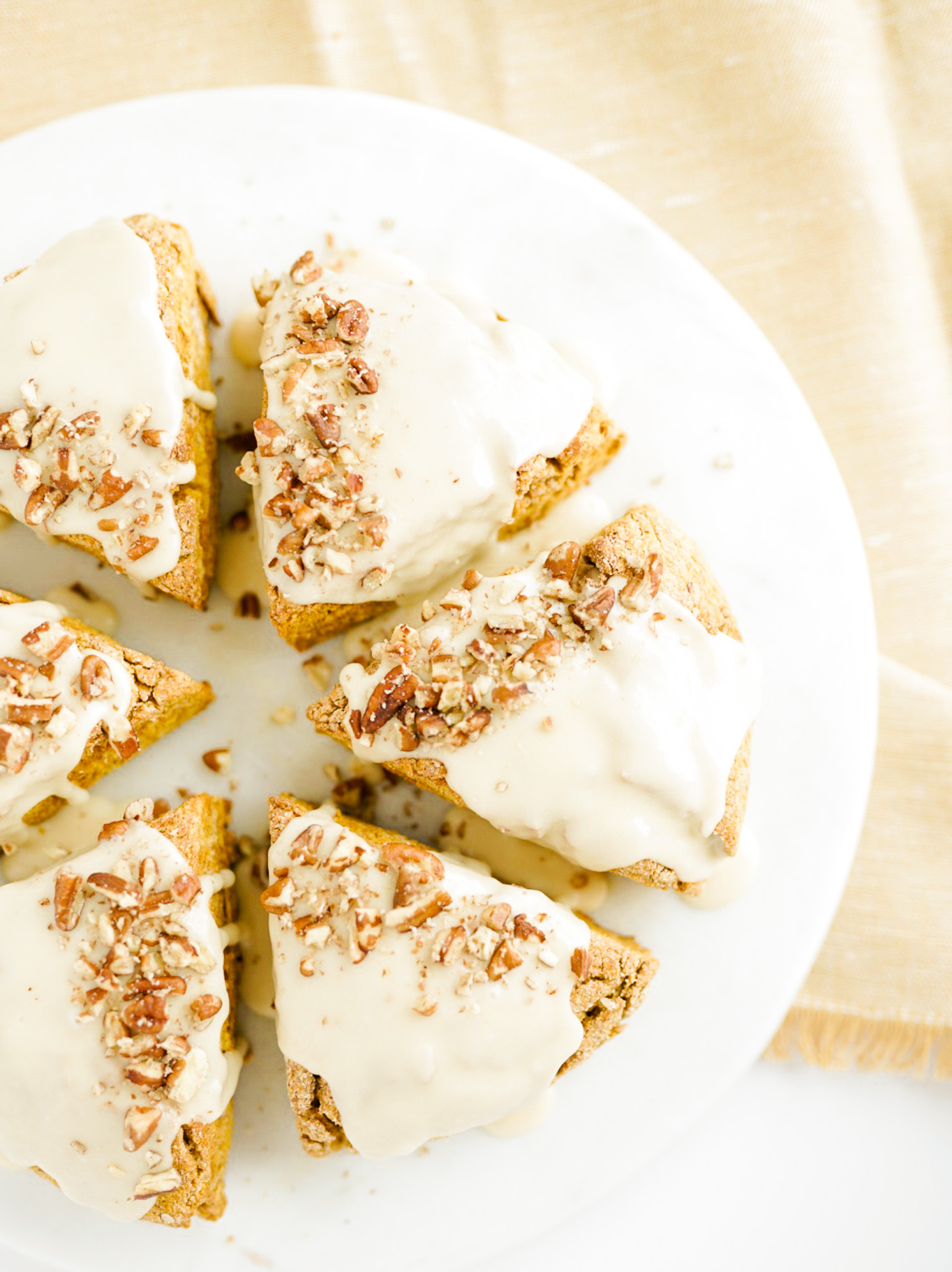 pumpkin scones with glaze and crushed pecans on white marble pastry board on gold dish towel