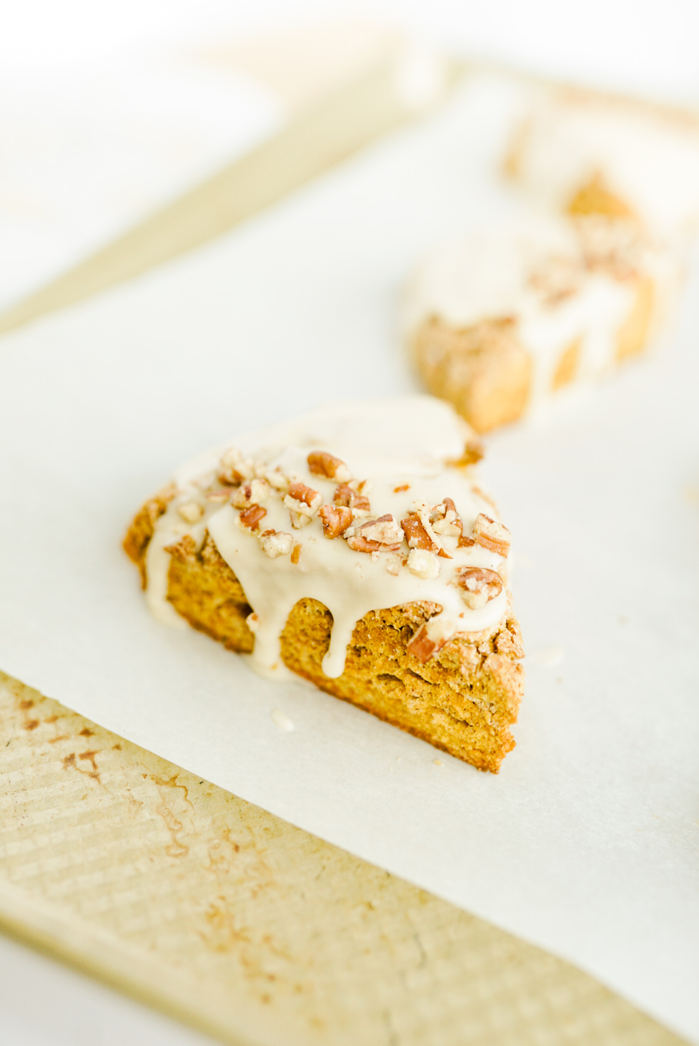 pumpkin scones with glaze and crushed pecans on white parchment paper on gold baking sheet