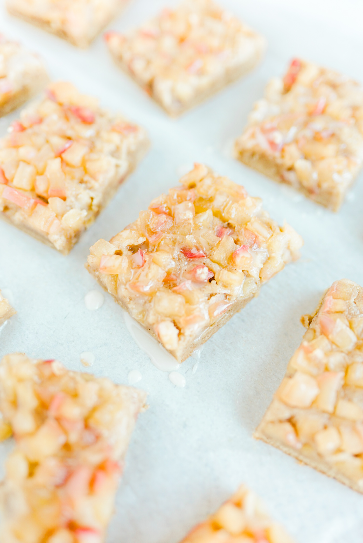 apple cider blondie squares with glaze on white parchment paper on gold baking sheet