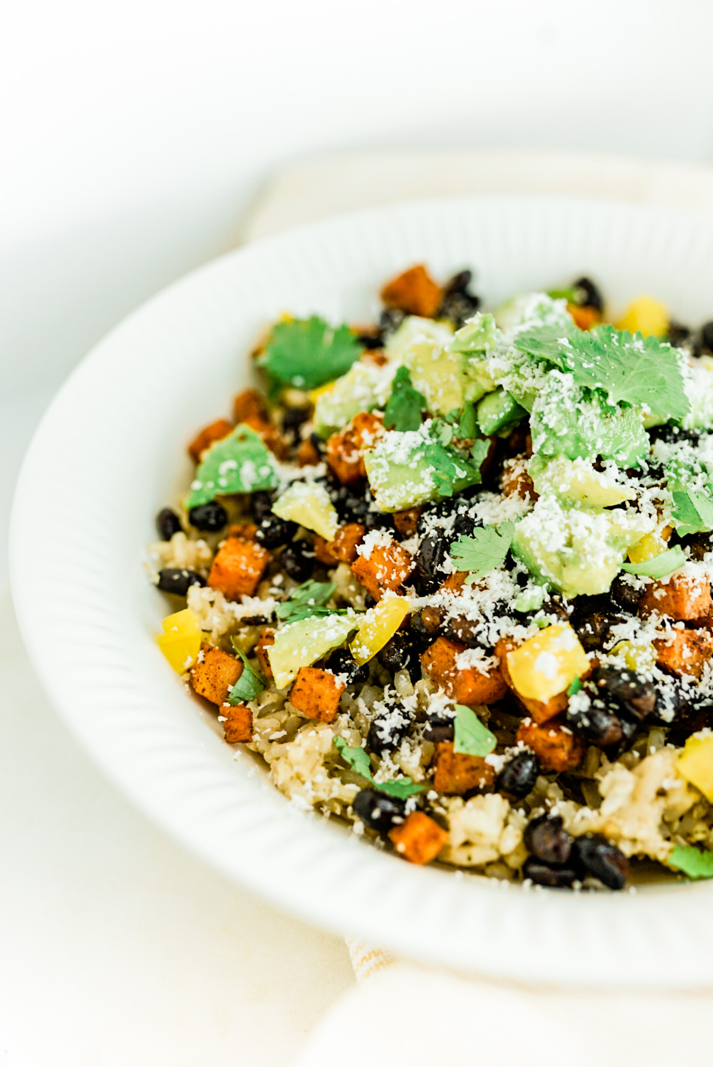 sweet potato black beans topped with avocado in white bowl on light yellow dish towel