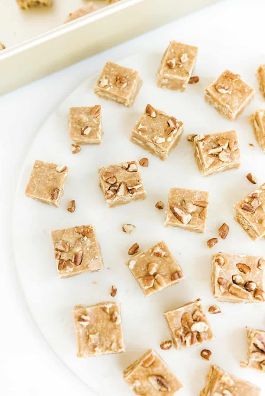squares of pumpkin pecan fudge on white marble surface with gold pan in background