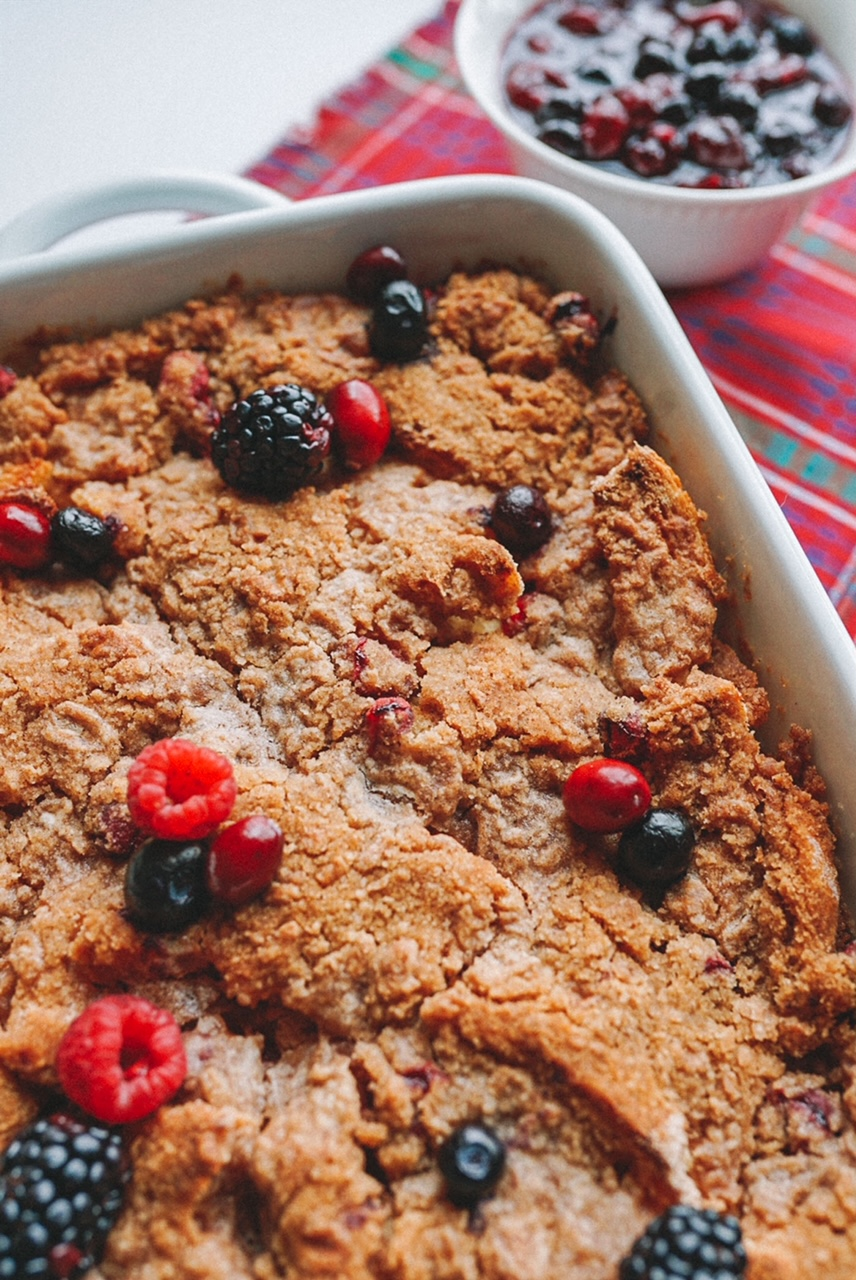 a slice of French toast bake with berries in white baking dish on red plaid napkin with mixed berry sauce in the background