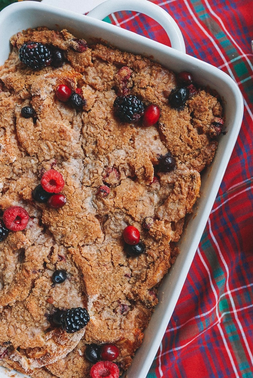 a slice of French toast bake with berries in white baking dish on red plaid napkin