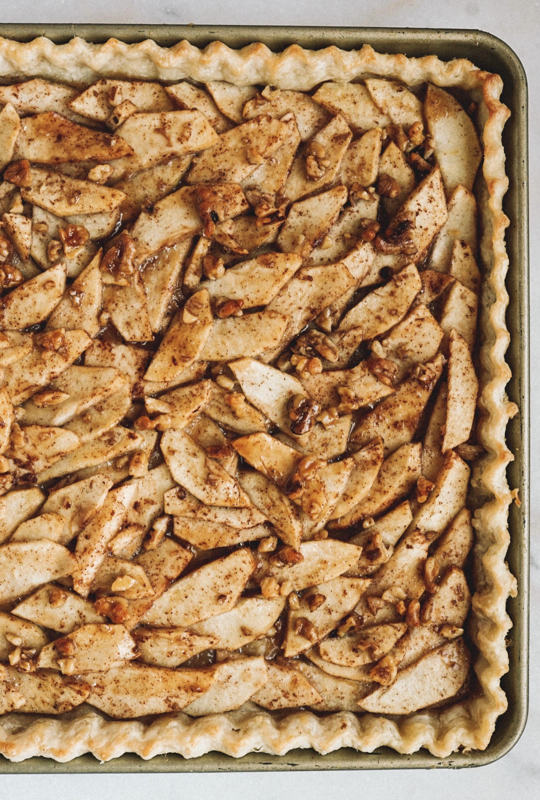 caramel apple slab pie with walnuts and caramel on top in gold baking sheet on marble counter