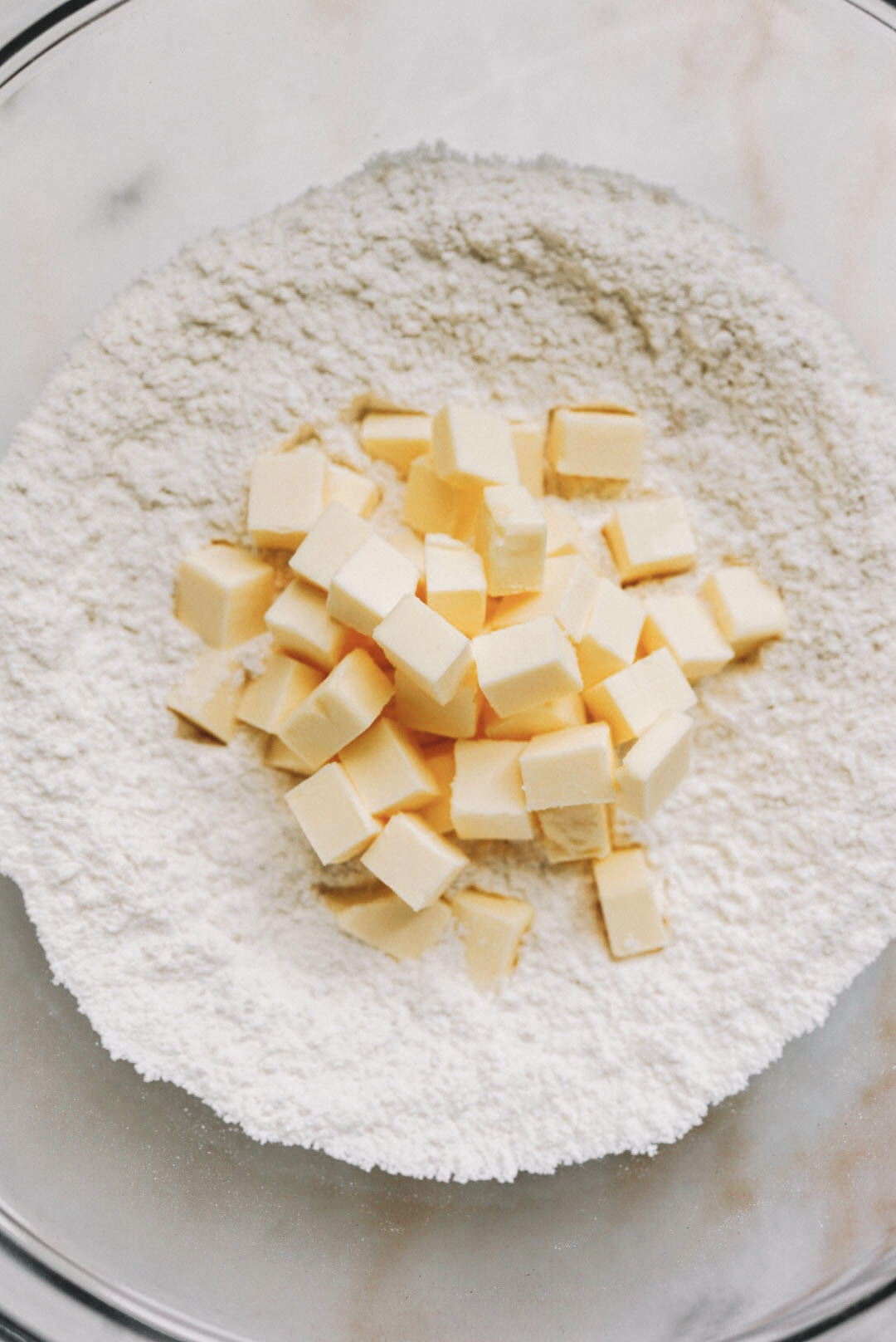 cubed butter on flour in glass bowl