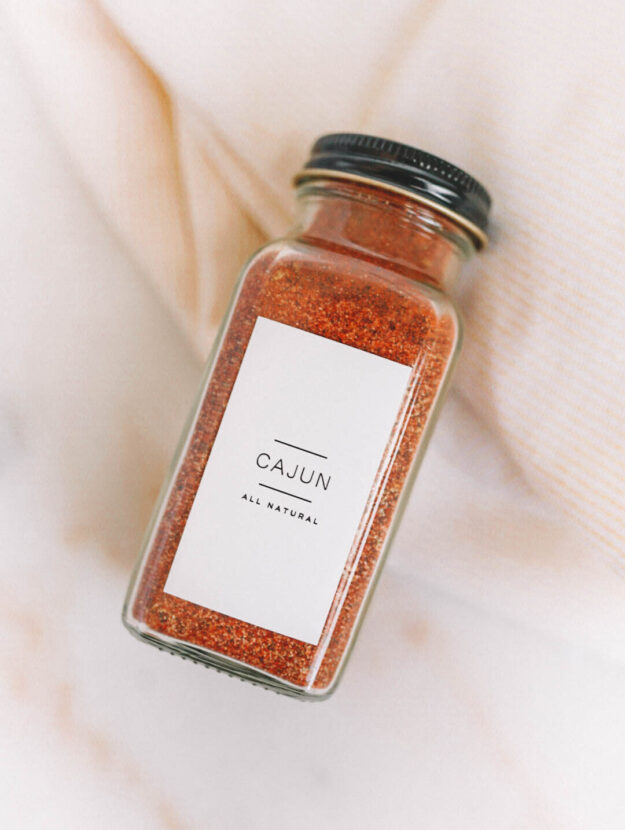 homemade cajun seasoning in glass jar with black lid and white cajun label on white marble counter