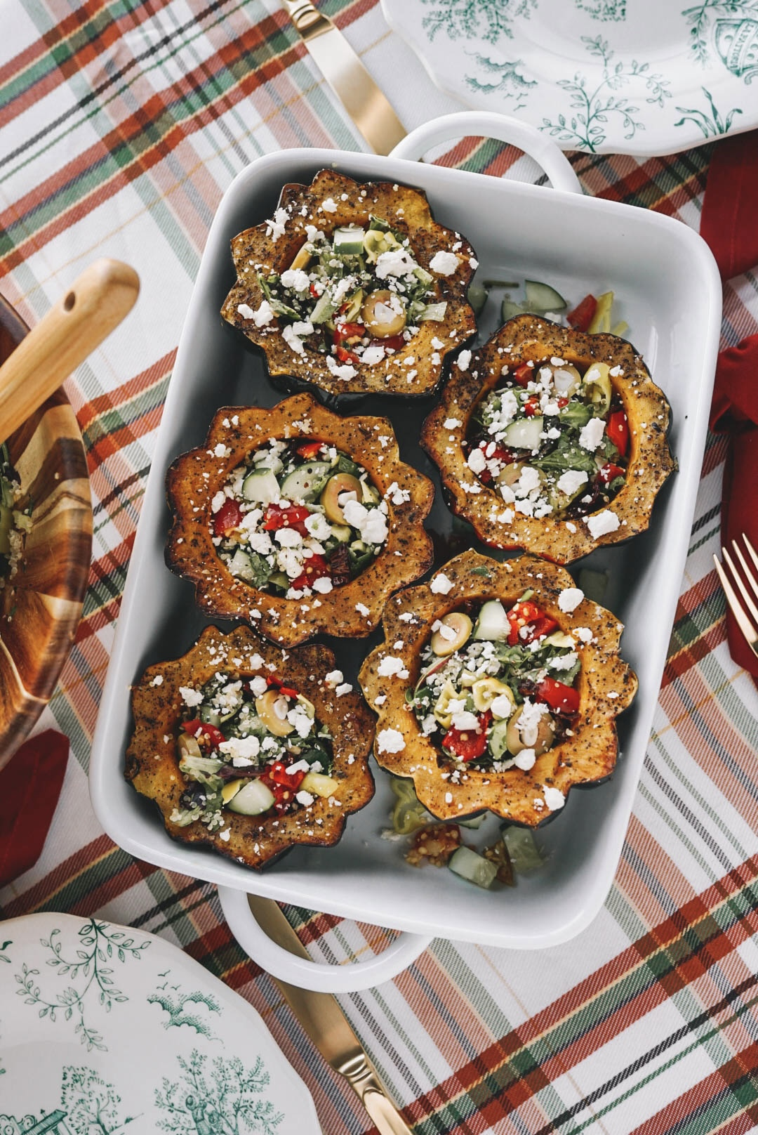 halved acorn squash roasted and stuffed with quinoa salad in white baking dish on plaid tablecloth
