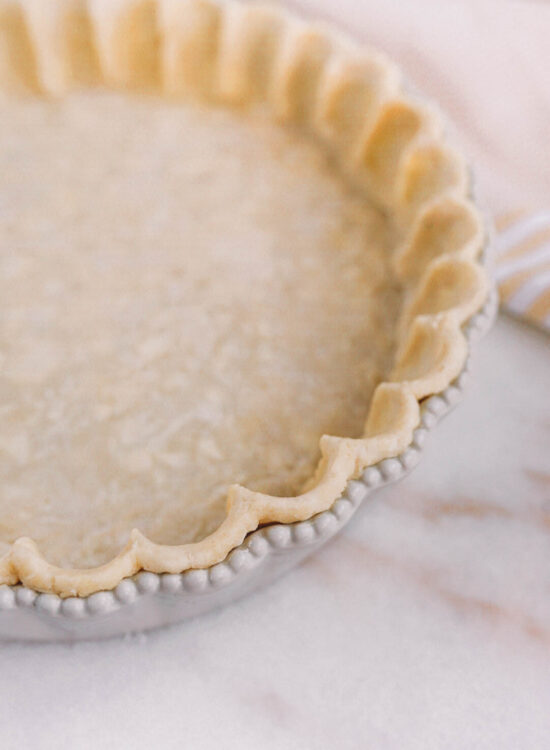 crimped pie crust dough in white scalloped pie dish on white marble counter with light yellow dish towel