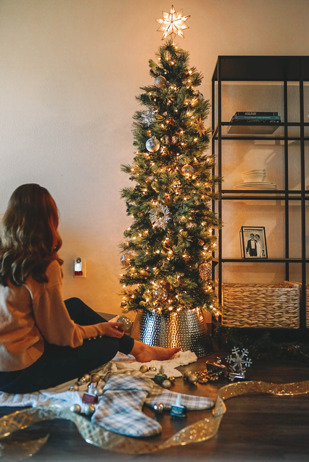 woman sitting in front of Christmas tree with lights and ornaments
