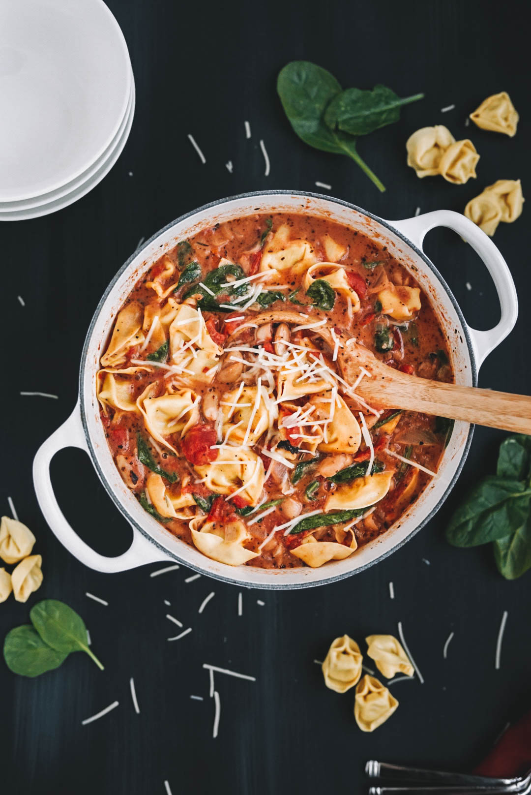 white le creuset dutch oven full of tortellini soup on black background