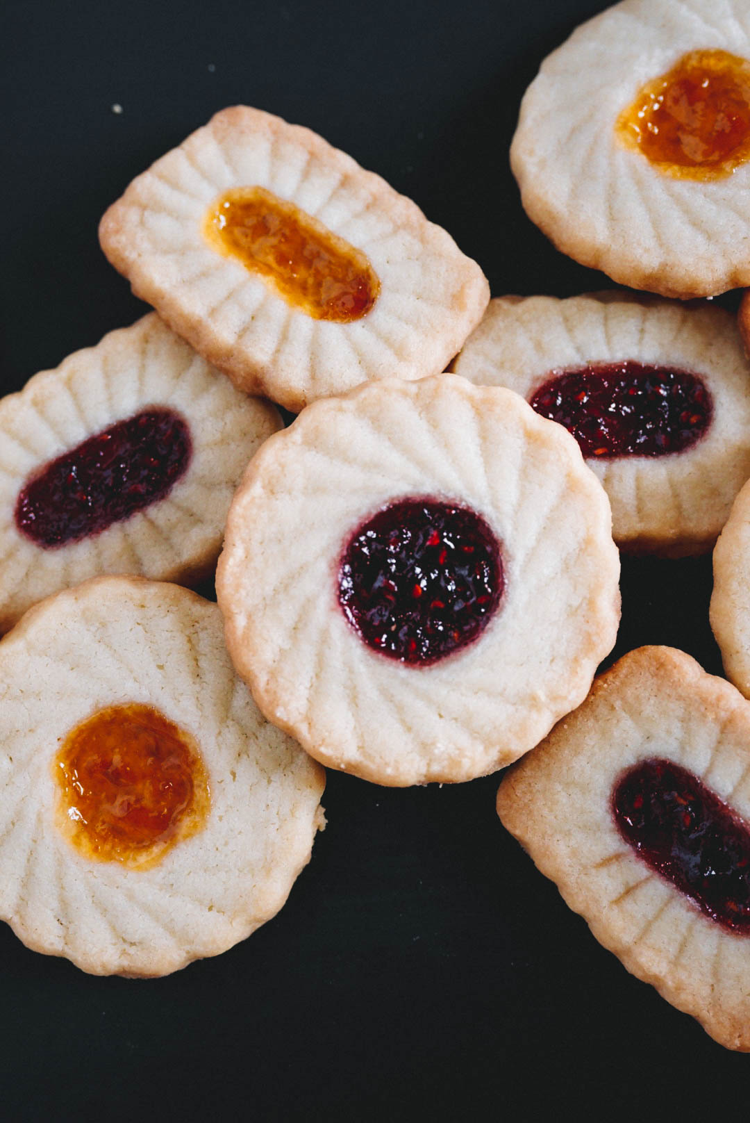 Round and rectangular thumbprint cookies on black backdrop