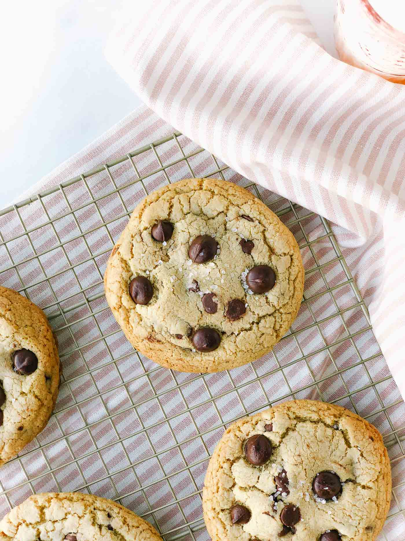 Brown butter chocolate chip cookies on gold cooling rack and light pink striped dish towel.