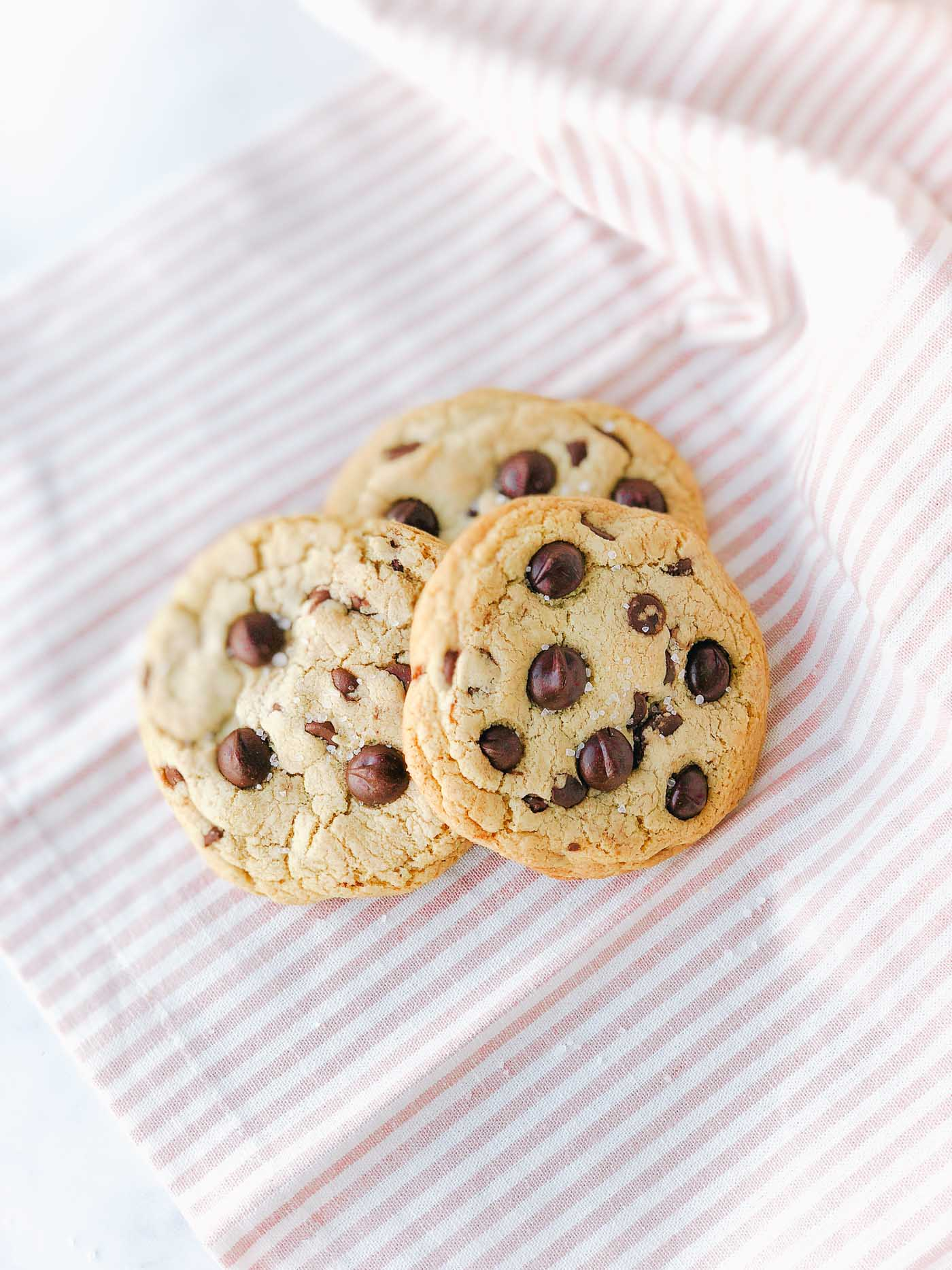 Brown butter chocolate chip cookies on light pink striped dish towel.