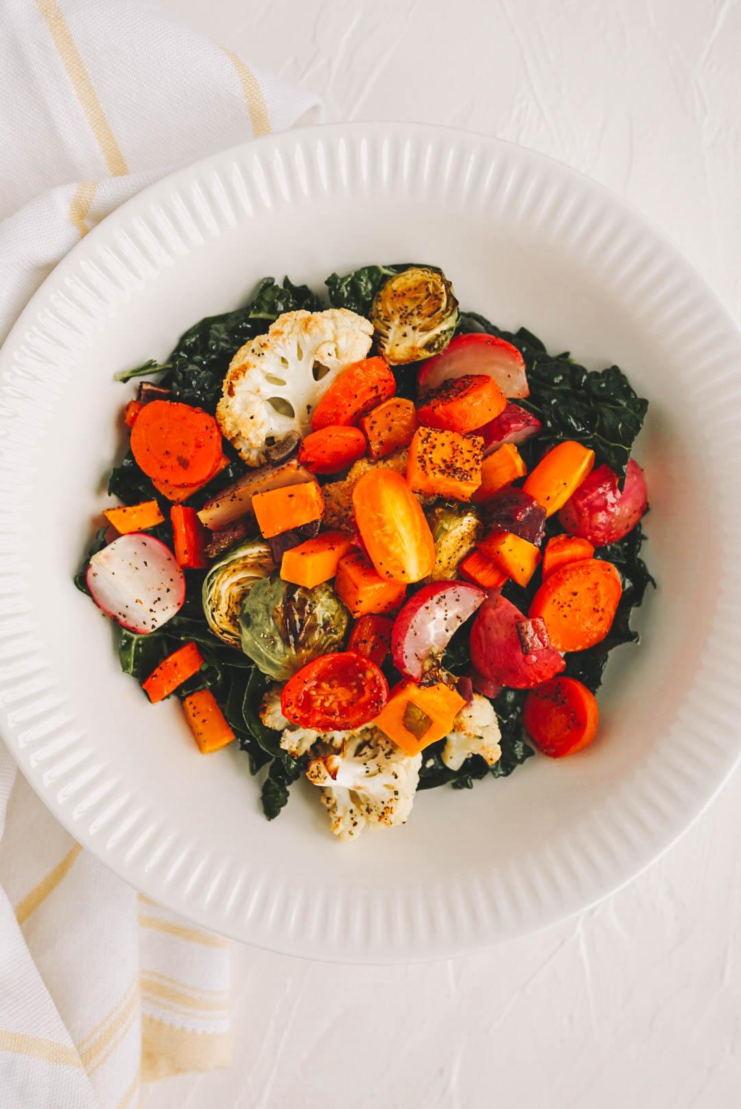 oven roasted vegetables on kale salad in white bowl
