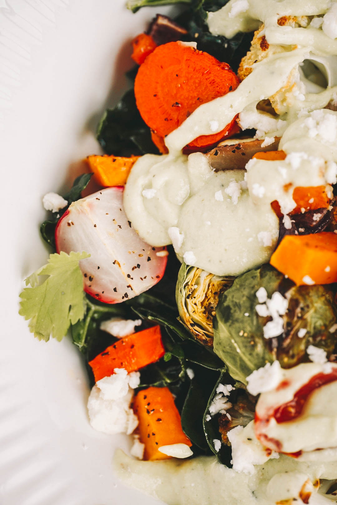 creamy salad dressing on veggies in white bowl