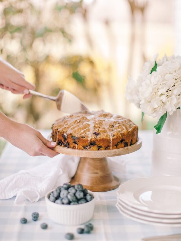 blueberry coffee cake recipe on wood cake stand on blue gingham tablecloth