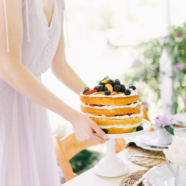 stacked peach shortcake with peaches and, blackberries, and whipped cream on white cake stand