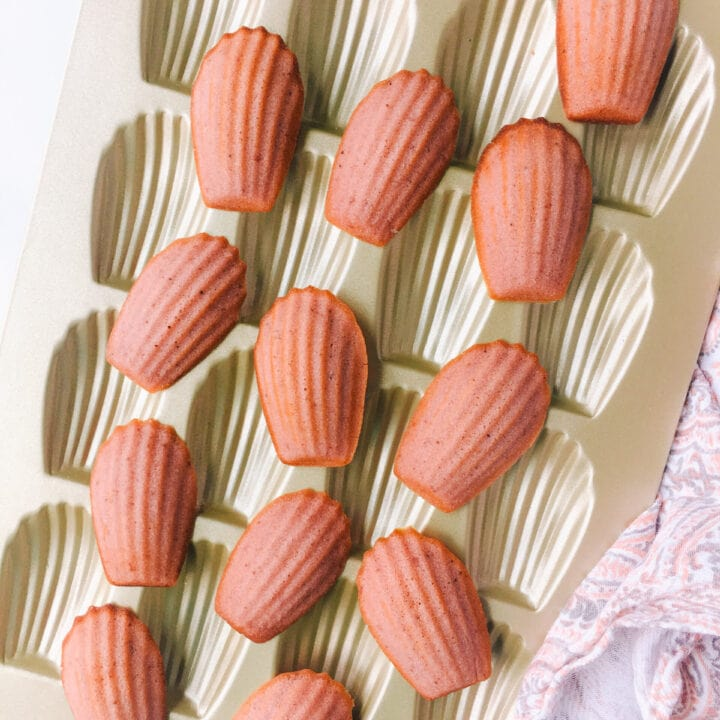 strawberry madeleine cookies on gold madeleine pan and light pink dish towel