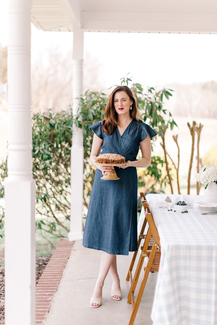 woman holding blueberry coffee cake recipe on wood cake stand