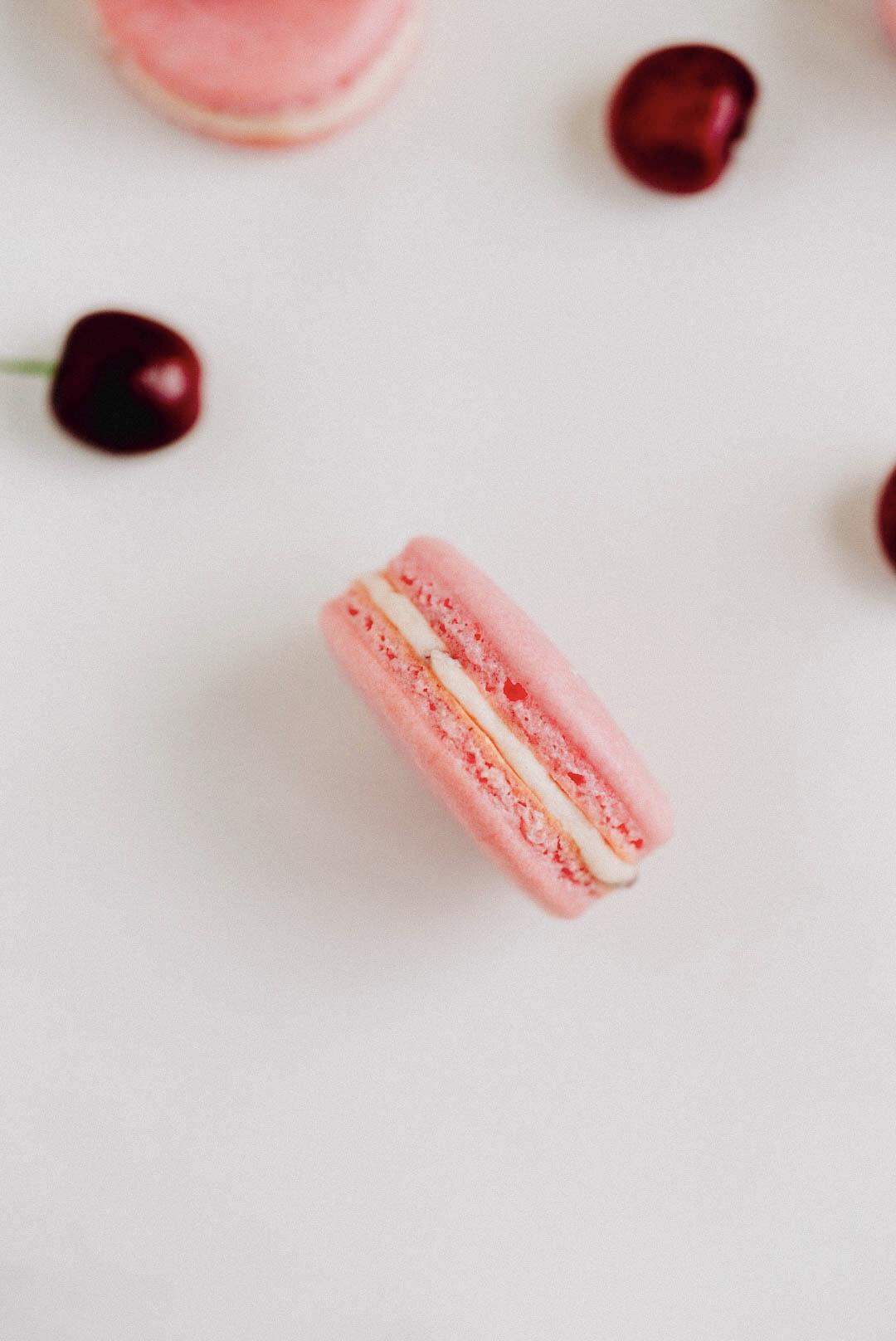 cherry vanilla macarons on white marble counter